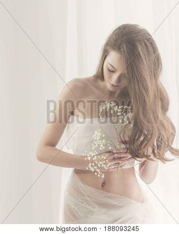 Lovely girl in white lingerie. Sensual photo. She holds white spring flowers near her breast.