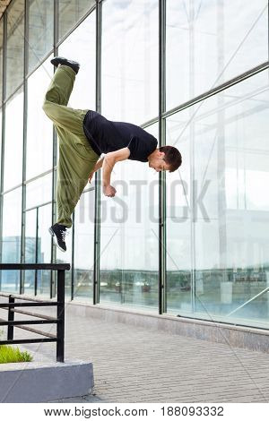 Young man jumps on a railing. Parkour in the urban space. Sports in the city. Sport activity.