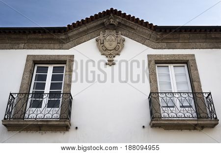Balconies and Coat of Arms carved in granite stone on the facade of a building in Ponte da Barca Portugal