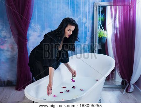 Woman in bath. Sexy brunette woman putting flowers to bathtube. Milk Spa concept