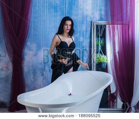 Woman in bath. Sexy brunette woman taking off her clothes before bath. She is wearing black sexual lingerie and looking at camera