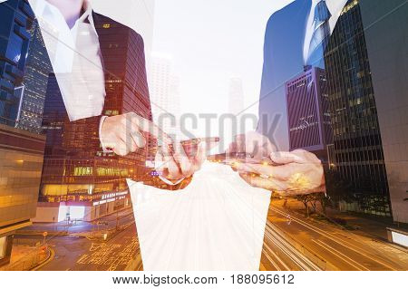 Double Exposure Of Business Man And Woman Using Smartphone With City Background