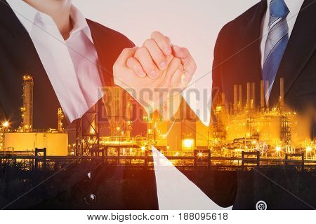 Double Exposure Of Arm Wrestling Between Businessman And Businesswoman With Oil Refinery Plant Backg