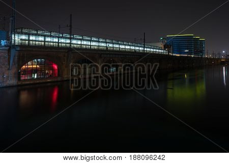 BERLIN - MARCH 05 2016: Railway platform city train (S-Bahn) and transfer to the subway station (U-Bahn) Jannowitz Bridge and the river Spree. Berlin at night.