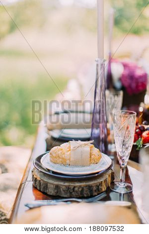 The side vertical photo of the croissant wrapped in the craft paper and rope and placed on the wooden stand at the background of the green forest