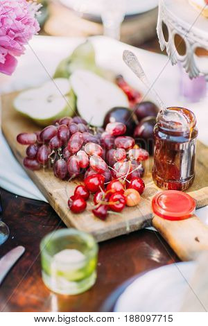 The composition of fruit. There are plums, green pears, dark grapes and juicy cherries are lying on the wooden board located near the bar of jar and small candle