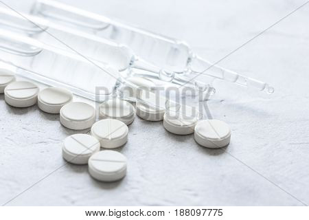 doctor's office table with medical pills and vials on white background