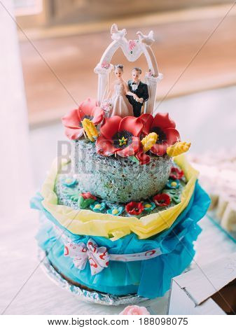 The huge blue wedding cake decorated with red flowers and the little figures of newlyweds