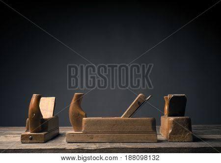 Three sides of an old wood plane on a rustic plank with space for text