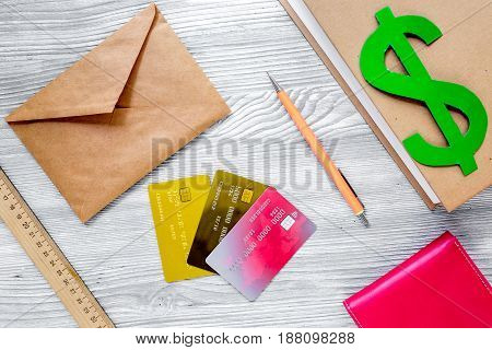 fee-paying education set with dollar sign, books and creit cards on light wooden table background top view mockup