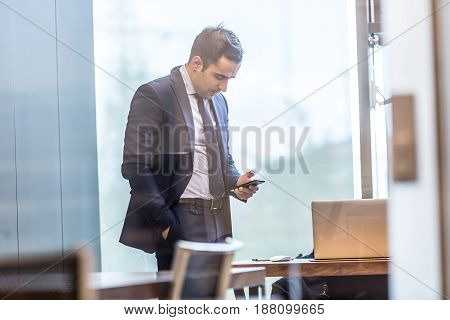 Through the window view of businessman looking at smart phone in modern corporate office.