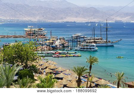 EILAT, ISRAEL - MAY 10, 2011: Central beach and marina in Eilat - famous resort and recreation city in Israel. This serene location is a very popular tropical getaway for Israeli and European tourists.