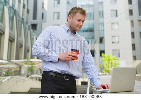 Businessman drinking coffee and working on laptop outdoor.