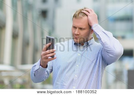 Distressed and confused businessman looking on his cell phone outdoors.