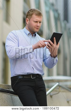 Businessman using a tablet pc against the background of office building.