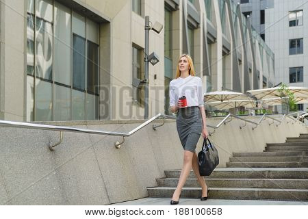 Businesswoman Walking On Street and Holding hot coffee.