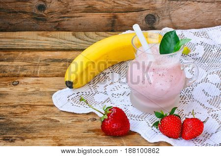 Strawberry banana milkshake on a lace tablecloth on a wooden table rustic style