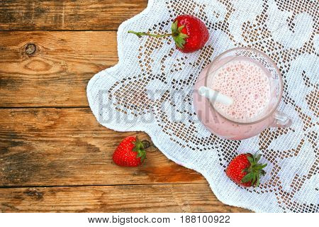 Strawberry milkshake in a glass on a lacy tablecloth on a wooden table rustic style top view flat lay