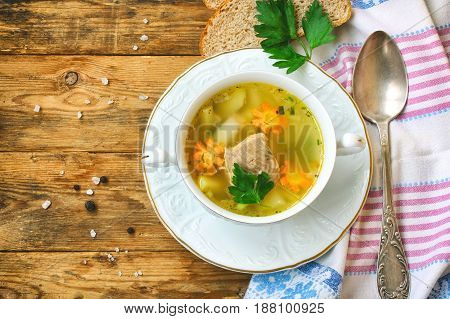 Fresh salmon fish soup with carrots and potatoes in a white bowl on a plate slices of bread napkin on a wooden table