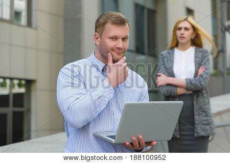 Clever businessman with laptop ahead of business lady who looks at him outdoor.