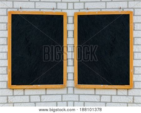 Two empty large slate boards with wooden frame on a stone wall.