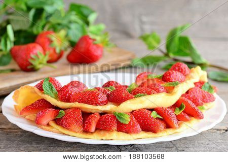 Low calorie omelette. Healthy and quick omelette stuffed with strawberries and garnished with mint leaves on a plate and vintage wooden background. Strawberry omelette recipe by diet. Closeup