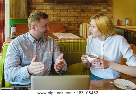 Business meeting in a cafe. happy or successful Man and woman are negotiating.