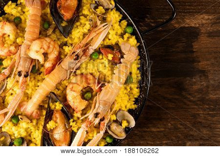 A closeup photo of a Spanish seafood paella in a typical paellera, with mussels, clams, and shrimps, with a place for text, shot from above on a dark rustic texture