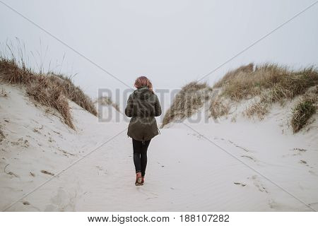 Woman walking on an empty beach in winter time