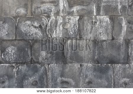Dirty gray and white brick wall. Front view