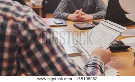 Business people in meeting room discussing financial report using data and gadget, close up