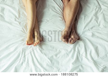 Low Section View Of Couple Relaxing And Lying On Bed At Home