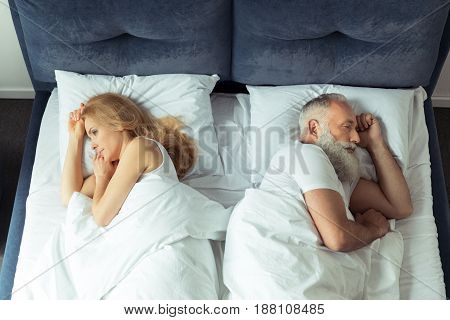 Top View Of Couple Lying In Bed Back To Back At Home