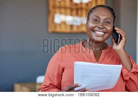 Portrait of a smiling young African businesswoman reading paperwork and talking on a cellphone while standing in large a modern office