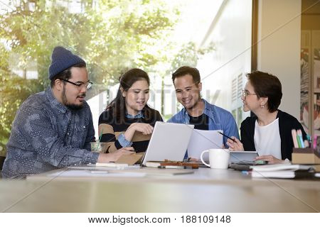 Group of business people having different age in creative business discussing work in coffee shop