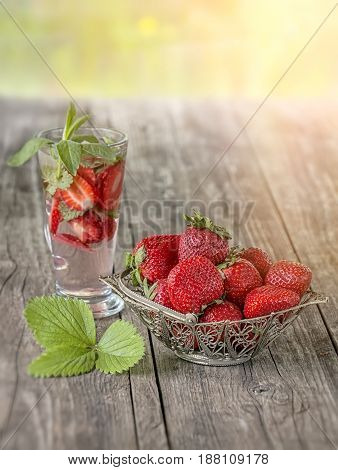 Strawberry openwork vase in the background of the glass with a strawberry drink on wooden table on a Sunny day.