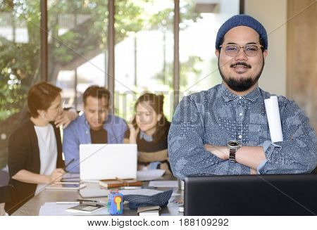 Young businessman smiling at camera in office