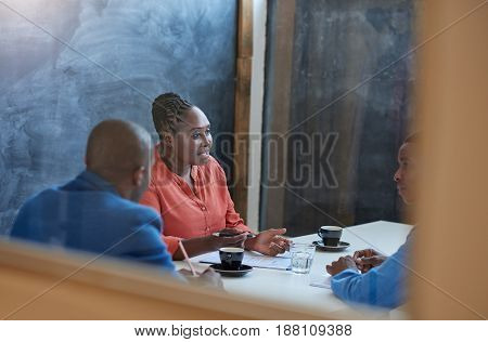 Focused young African businesswoman talking to two male colleagues while sitting together in a boardroom in a modern office