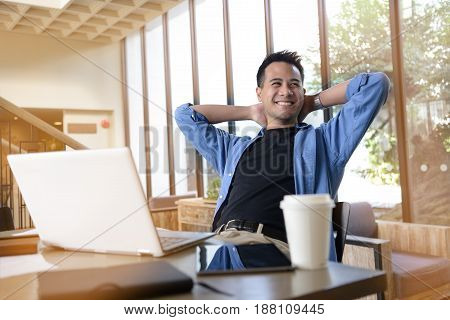 Happy young businessman working on laptop while sitting at his working place in office