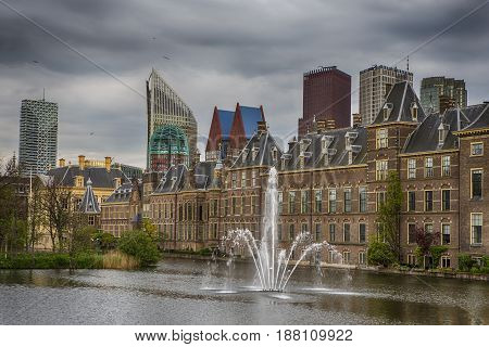 Binnenhof Palace of Parliament inThe Hague in The Netherlands before the Sunset. Against Dark Grey Clouds with Modern Skyscrapers on Background. Horizontal Image
