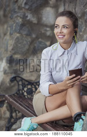 Youth Lifestyle Concepts. Pretty Smiling Caucasian Brunette Woman Relaxing on Bench and Listening to Music on Smartphone. Vertical Image Orientation