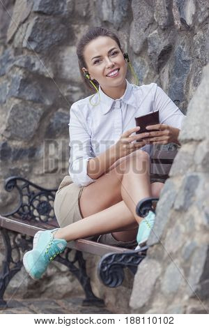 Youth Lifestyle Concepts. Happy Smiling Caucasian Brunette Woman With Headphones Relaxing on Bench and Listening to Music on Smartphone. Vertical Image