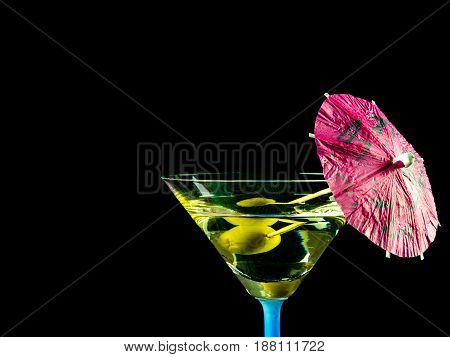 Cocktail glass with black background martini drink with olive and pink decotative umbrella