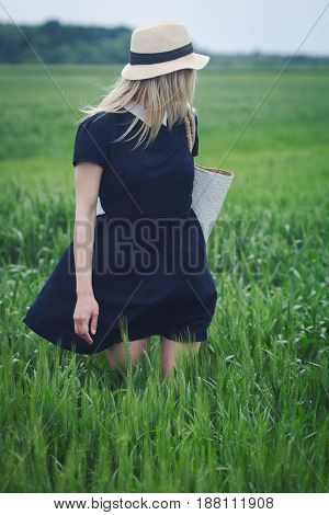 front view of beautiful Caucasian woman with wicker hat and white bag on her shoulder wearing a black dress looking back in a green field of wheat