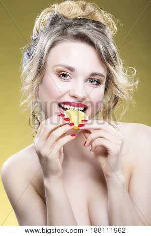 Sexy Fruit Series. Portrait of Cute Funny Naked Caucasian Girl Holding Lemon Slice In Front of Her Mouth. Posing Against Yellow Background. Vertical Image Orientation