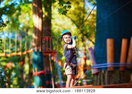 Young Boy Passing The Cable Route High Among The Trees, Extreme Sport In Adventure Park