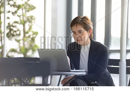 Executive businesswoman working with laptop computer at outdoor cafe