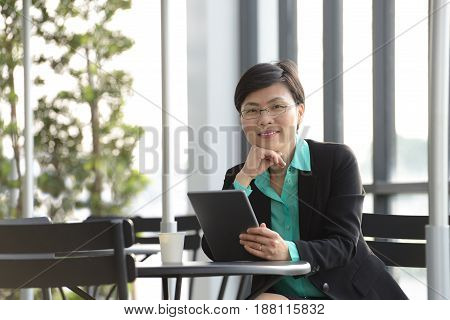 Businesswoman working with tablet computer at outdoor cafe
