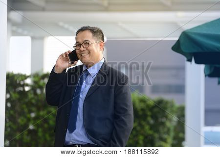 Executive businessman talking on a mobile phone at outdoor office