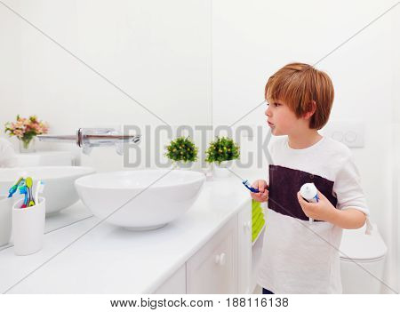 Happy Young Boy Brushing Teeth In Bathroom